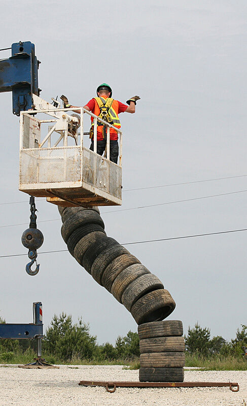 Video still of a construction worker and a sculpture of tires.