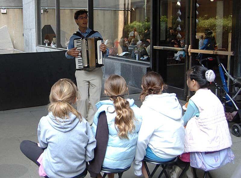 Kids listen to an accordion player