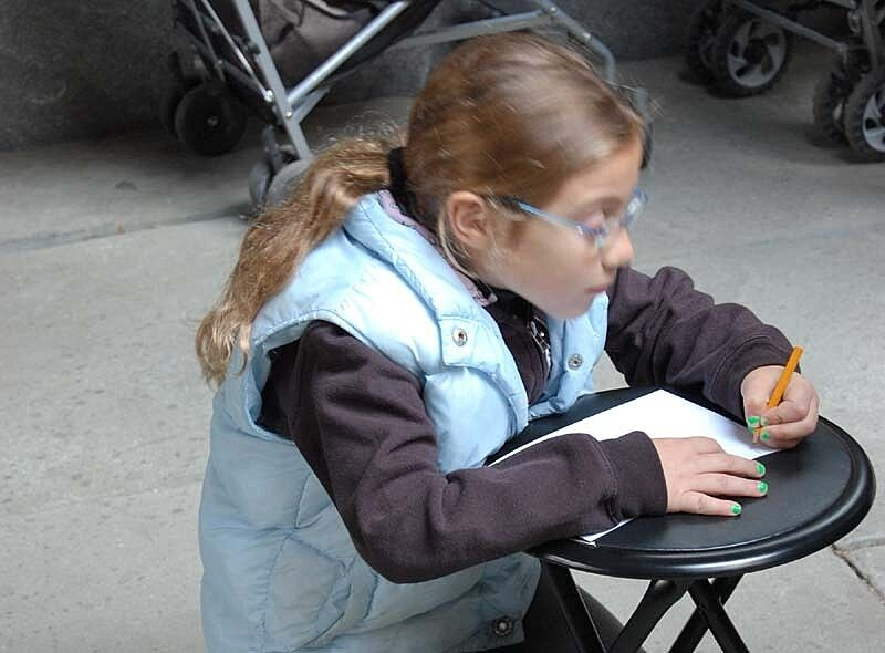 A girl writes on a piece of paper