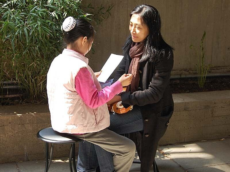 A girl reading to her mother