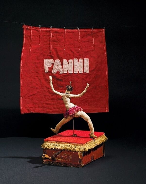 A cloth sculpture of a belly dancer on a red podium.
