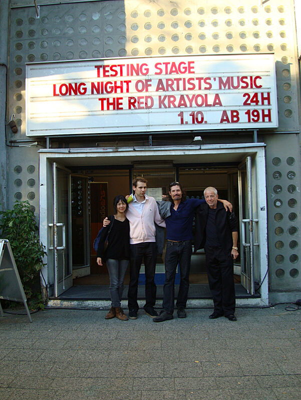 A photograph of four people standing in front of a venue.