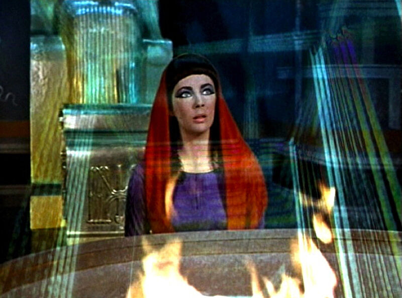A video still of a woman wearing a red head scarf looking up.