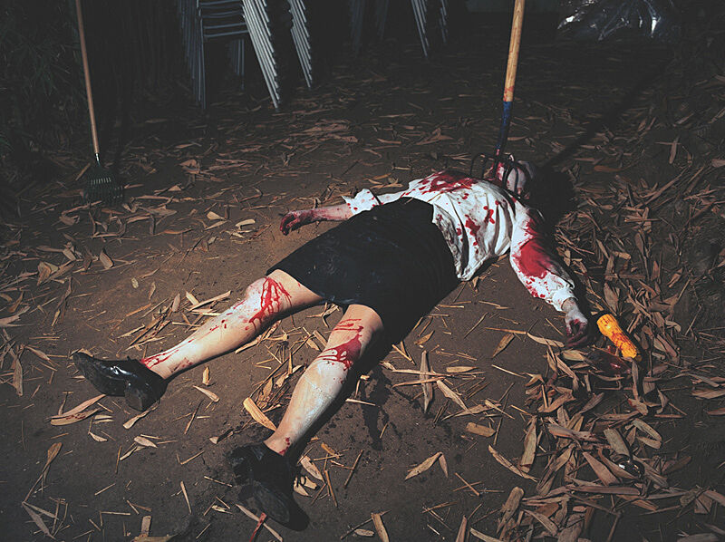 A person lying on the floor covered with blood.