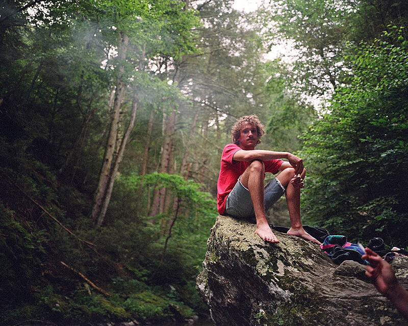 A photograph of a person sitting on a rock in a forrest.