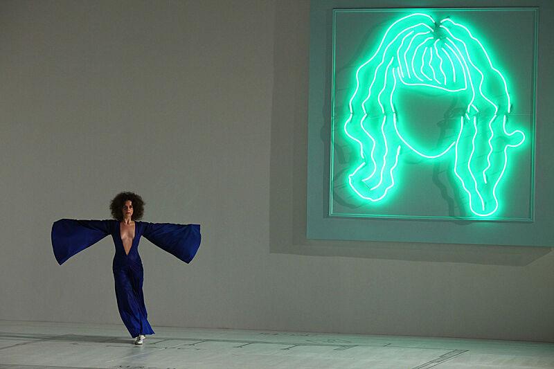 Woman dancing next to neon artwork.