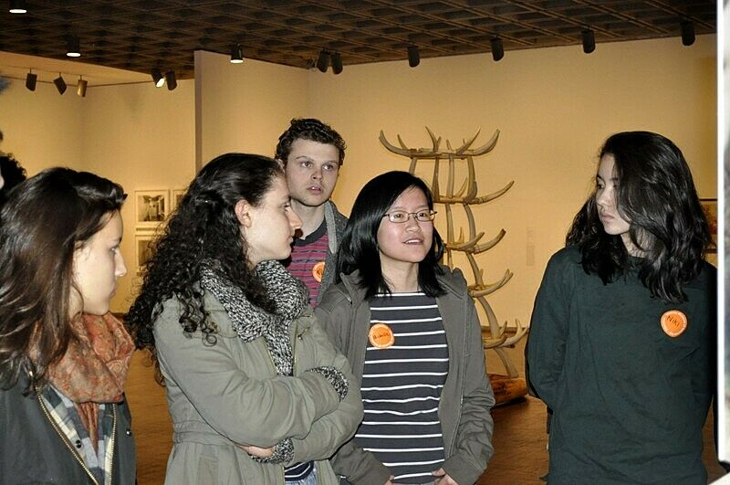students standing in room of artwork