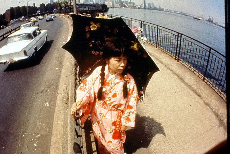 A projection of a women wearing a kimono and holding a parasol by the highway and river.