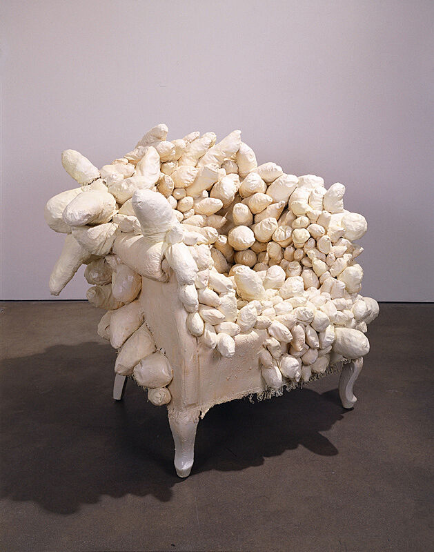 White chair covered in stuffed objects.