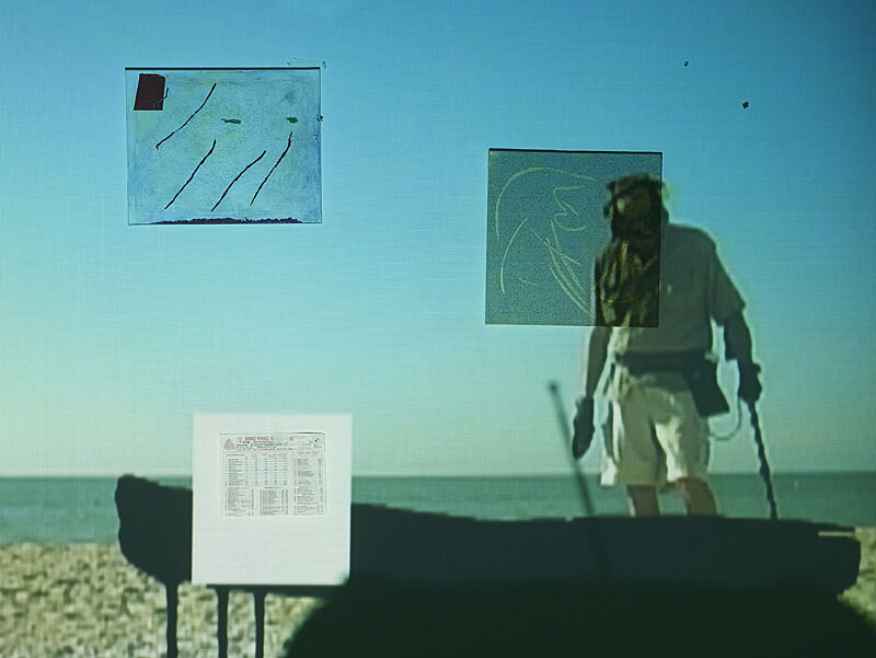 A video projection of a man with a metal detector on the beach, on top of other materials and documents.