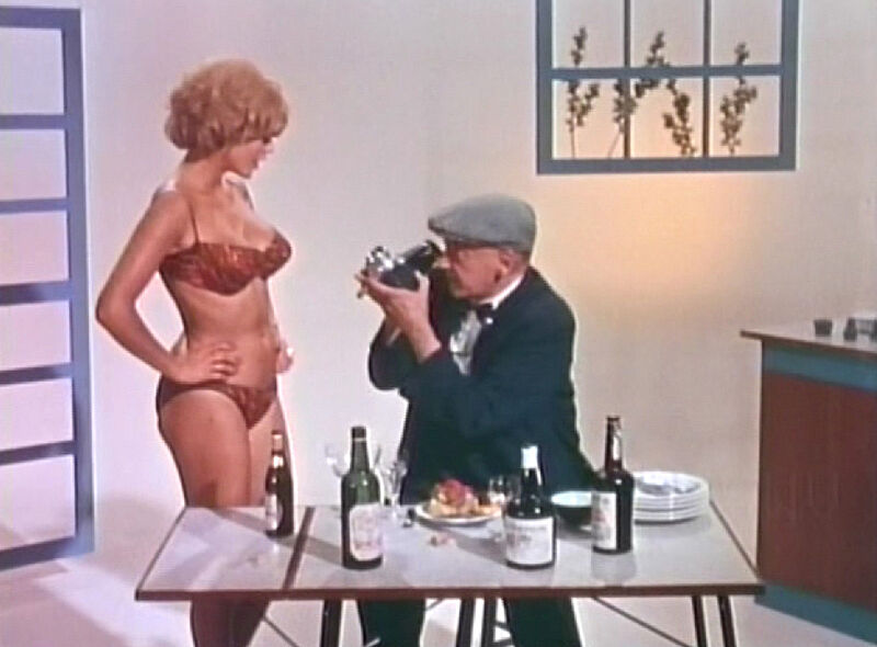 A still from a film. A seated man points a camera at a woman in her underwear.