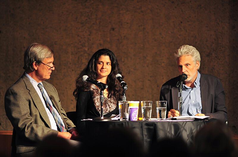 The panelists Robert Langan, Janine Antoni, and Lyle Rexer around a table.