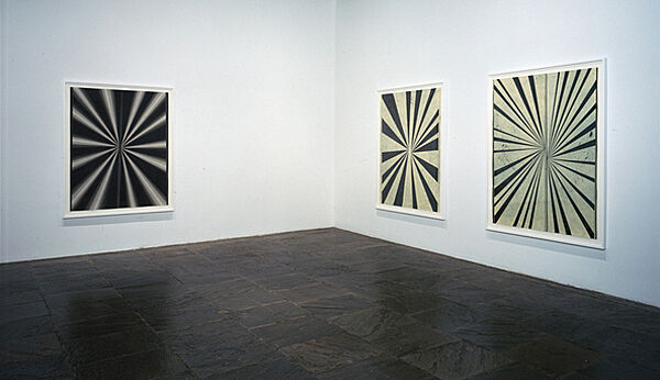 Three artworks with black and white stripes on the wall of a gallery.