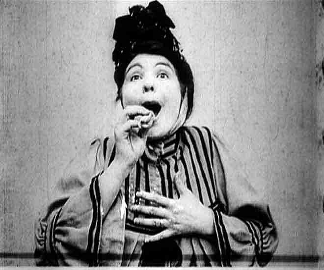 A woman starts to eat something in a black and white photo.