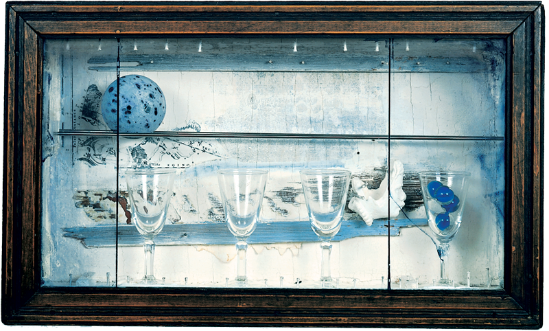 A glass framed wooden box with glassware and objects inside.
