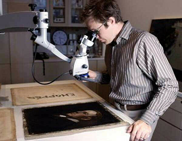 conservator looks under microscope at artwork