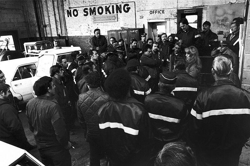 Crowd of workers huddle to door