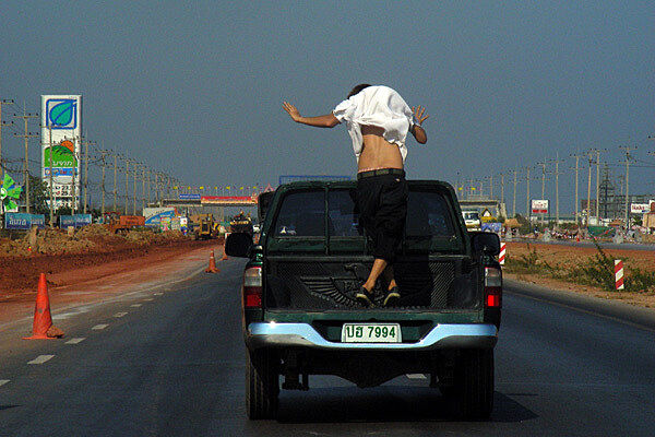 Man standing on top of truck driving.