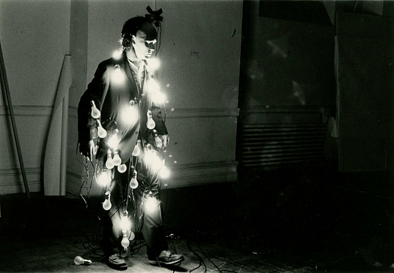 The artist Jared Bark, masked and wrapped in a string of light bulbs.