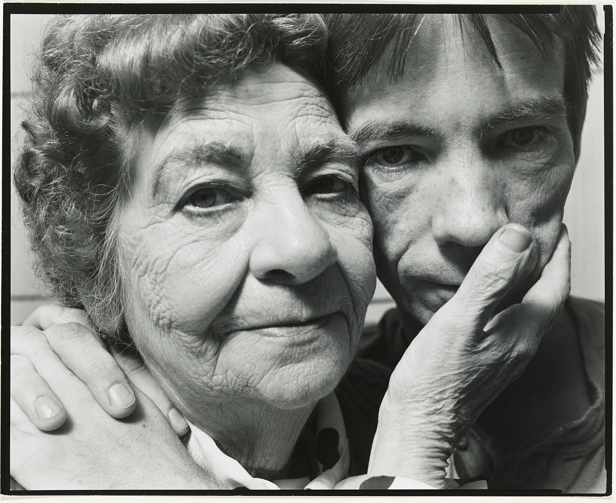 A black-and-white photograph by Nicholas Nixon. A woman touches the face of a younger man.