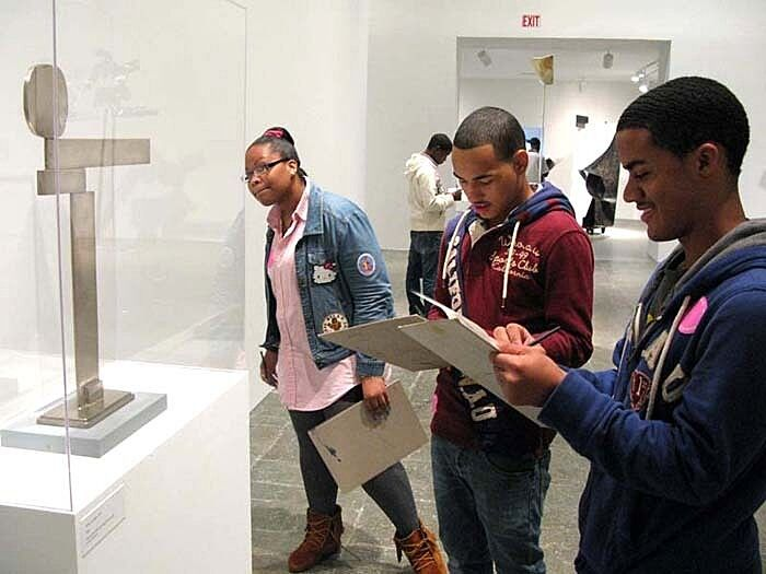 three students with notepads in front of sculpture