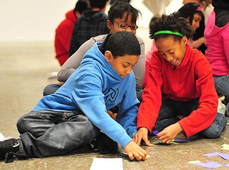 students sit on floor discussing art