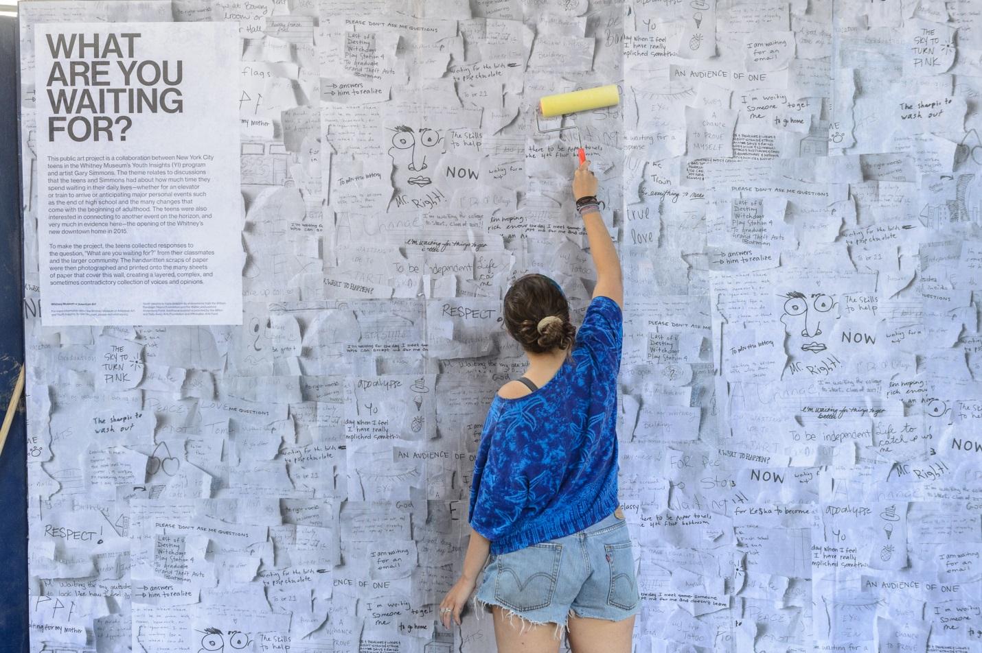 A teen putting up an outdoor poster