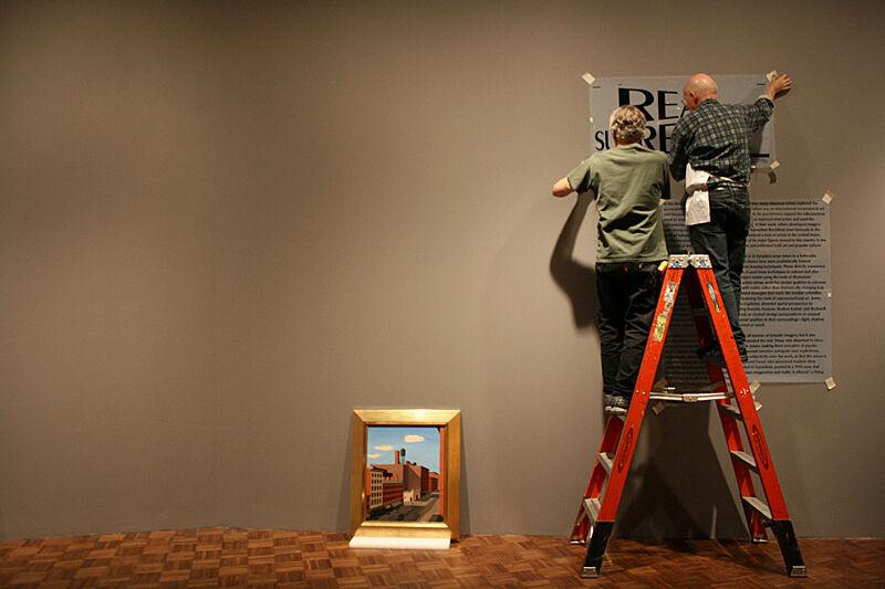 Men installing an exhibition sign.