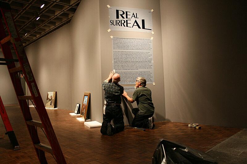 Men installing exhibition description sign.
