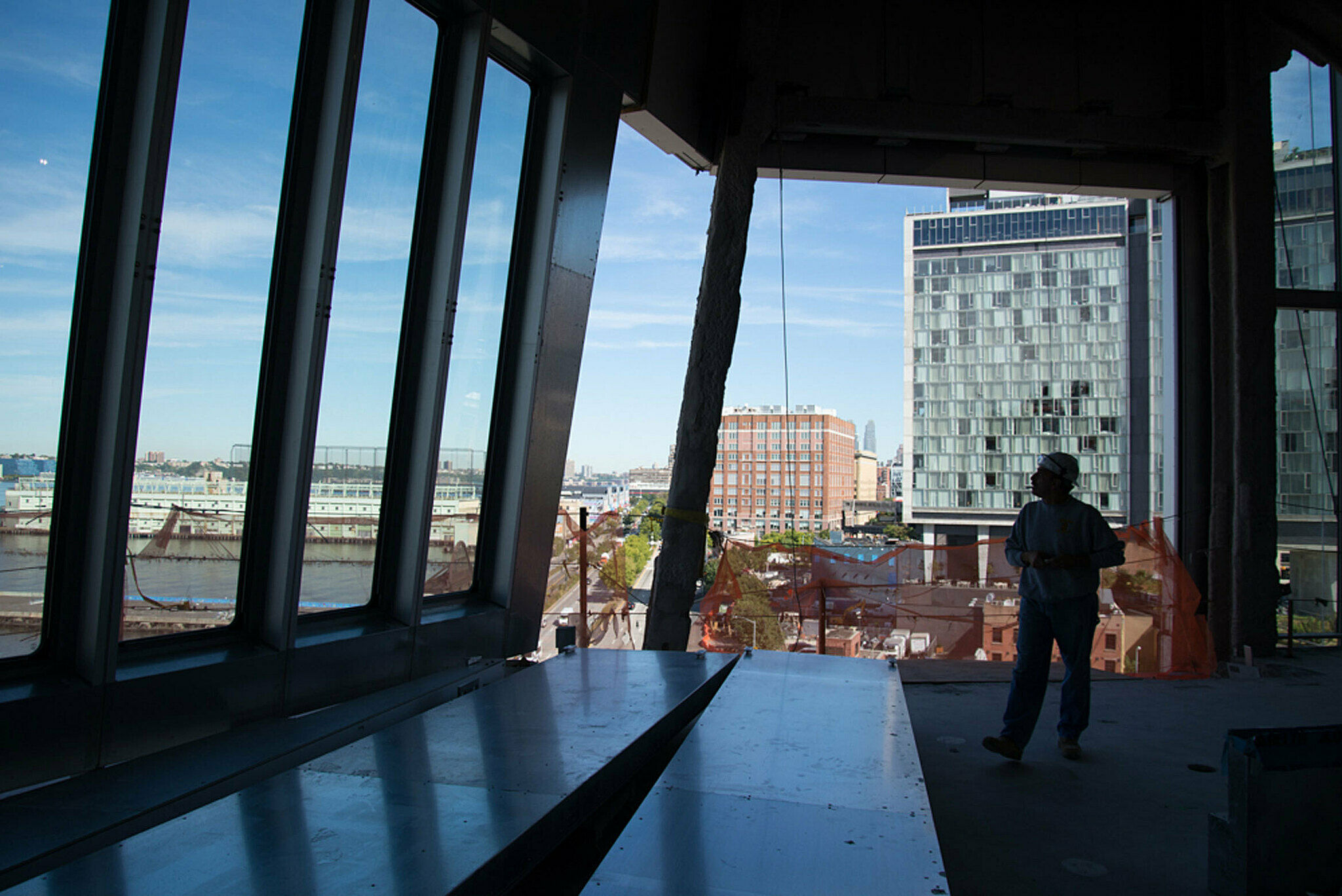 Man looking out on Hudson from large windows.