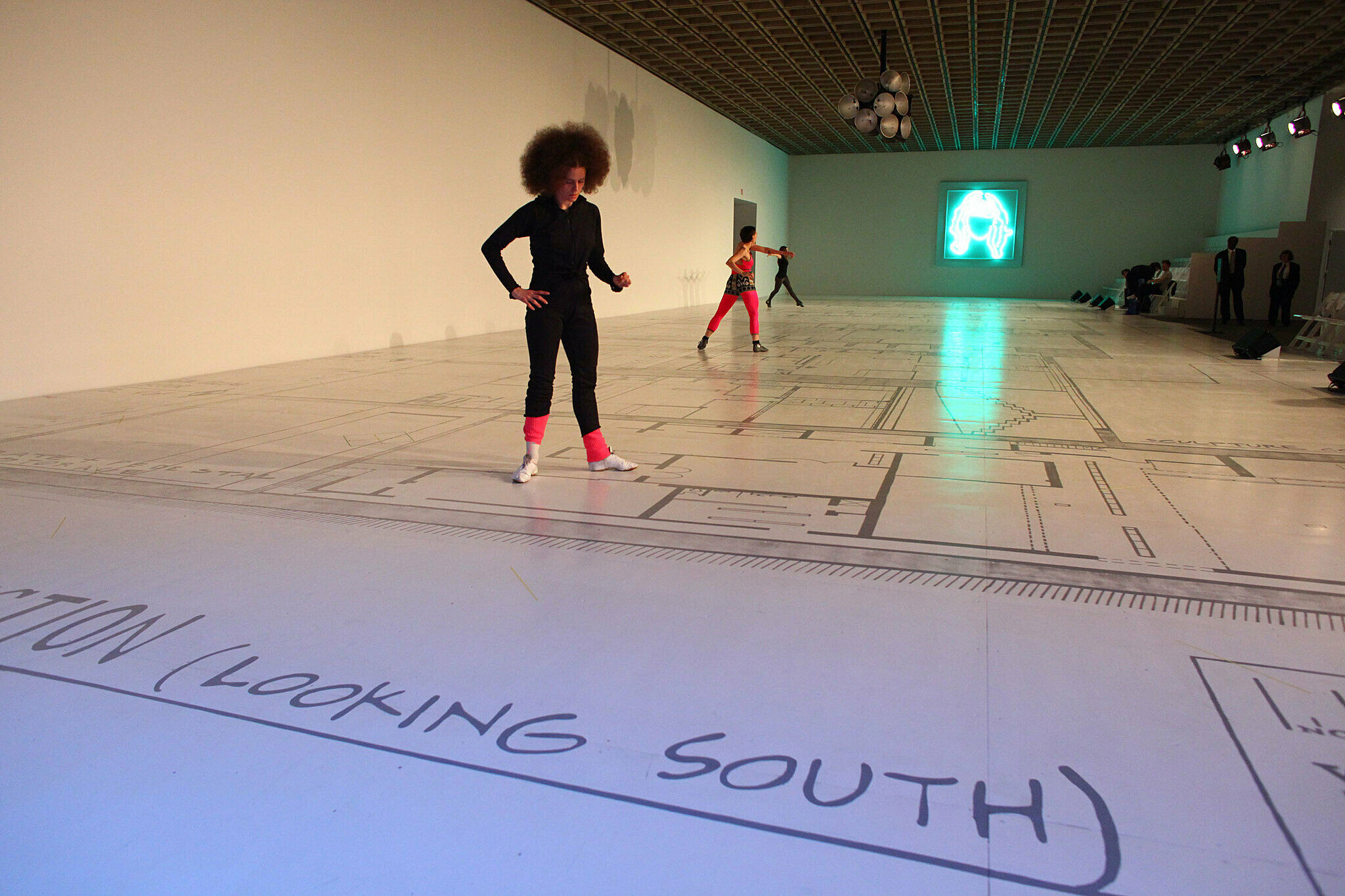 Three dancers stand on a floor plan of the Whitney.