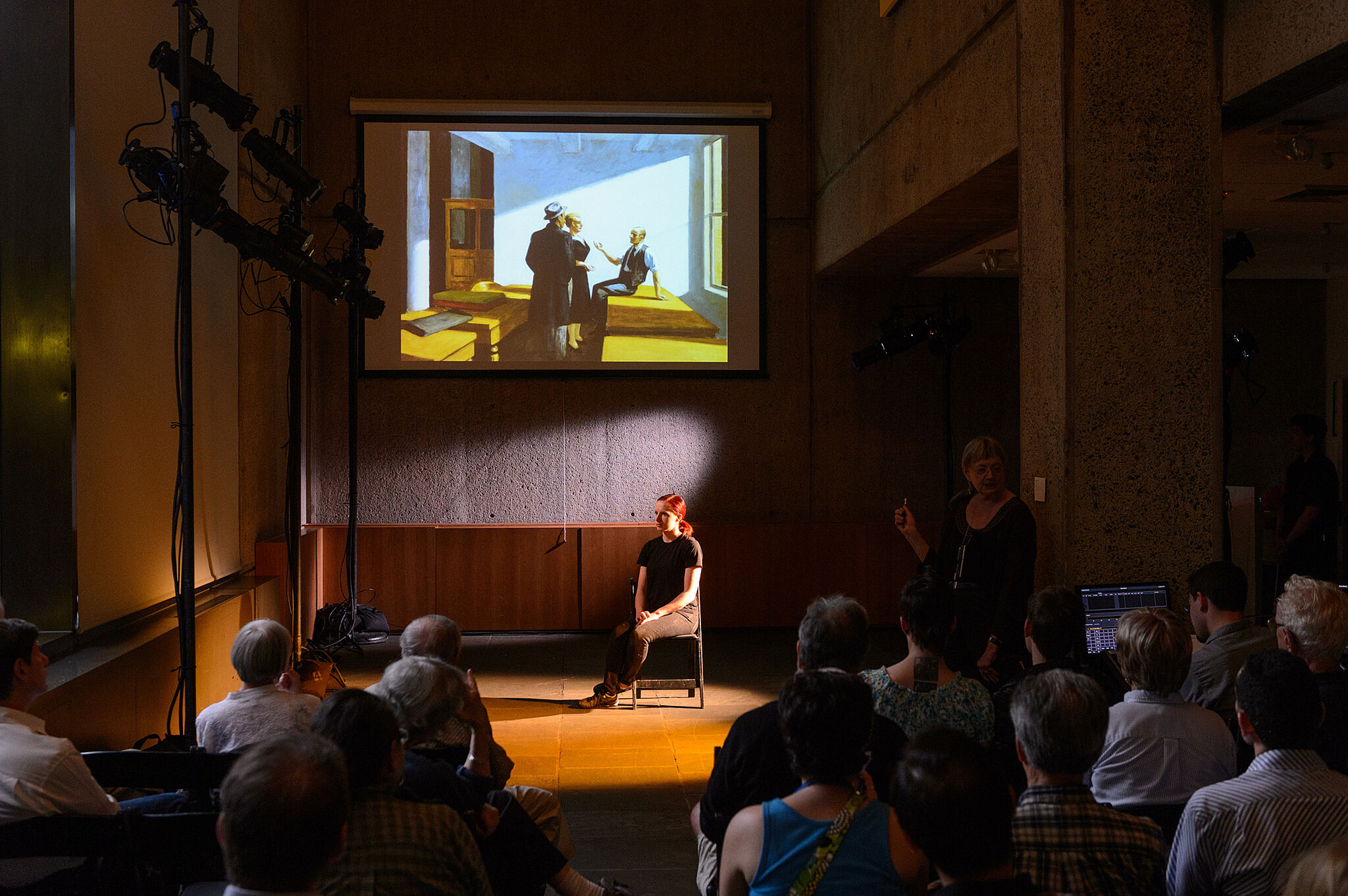 Woman acting on stage in chair with projection.