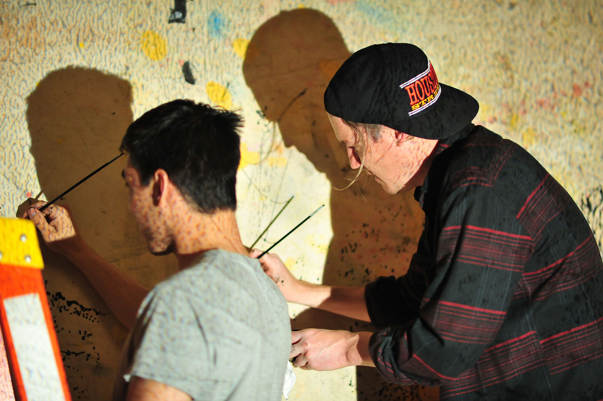 Two students painting on wall.