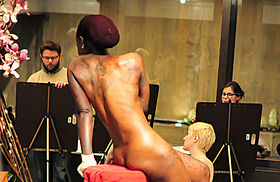 Nude model with students painting around her.
