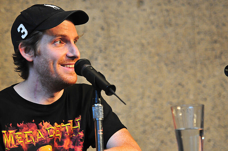 Cory smiling in front of a microphone.
