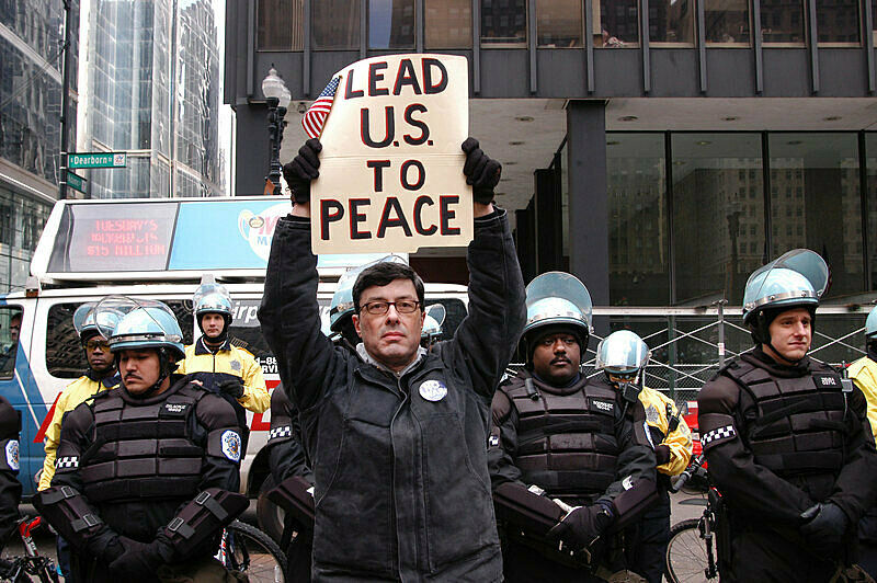 A man holding a protest sign in front of policemen in the street.