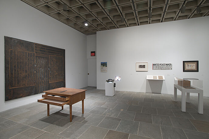 An installation of wood desks and artworks on the wall.