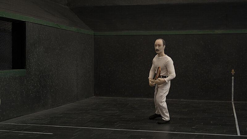 A still shot from a video of a man playing tennis.