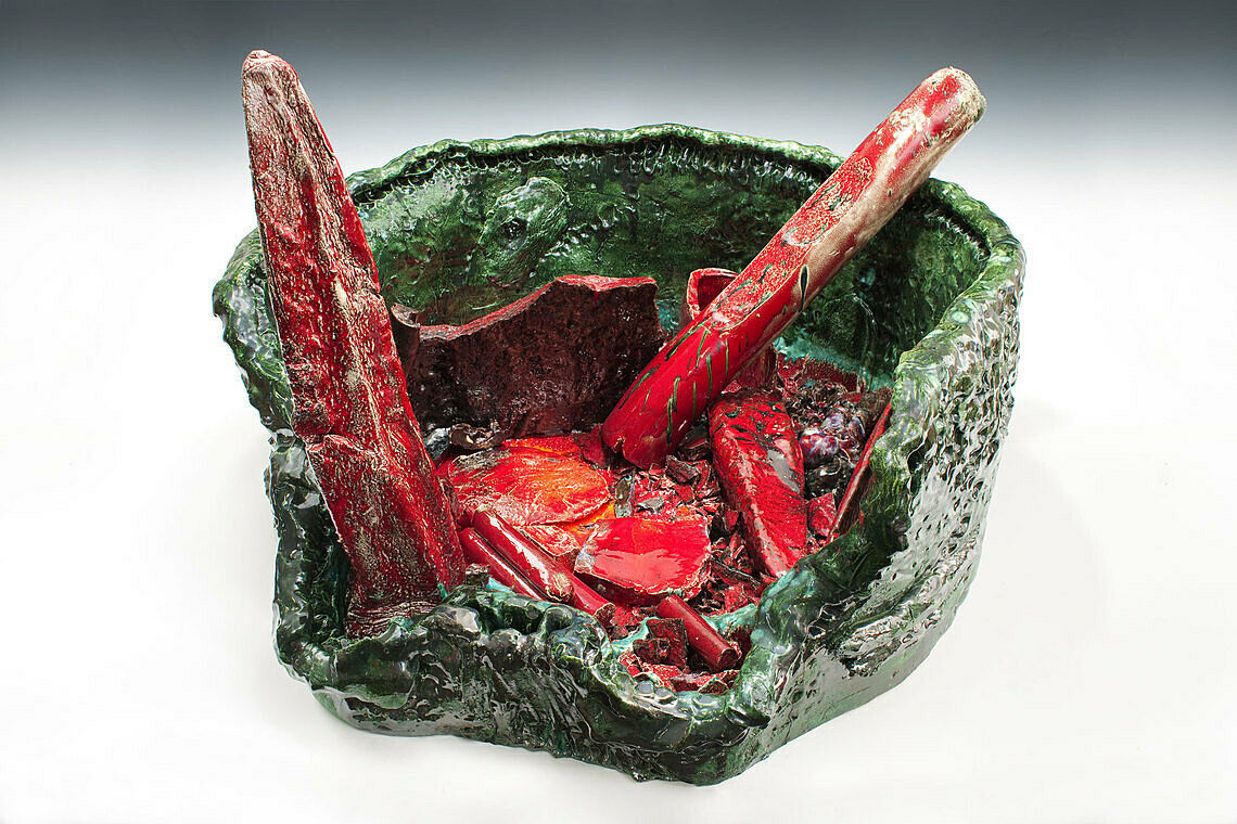A ceramic work in green and red of a broken basin.