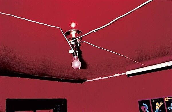 A lightbulb attached to the ceiling of a red room.