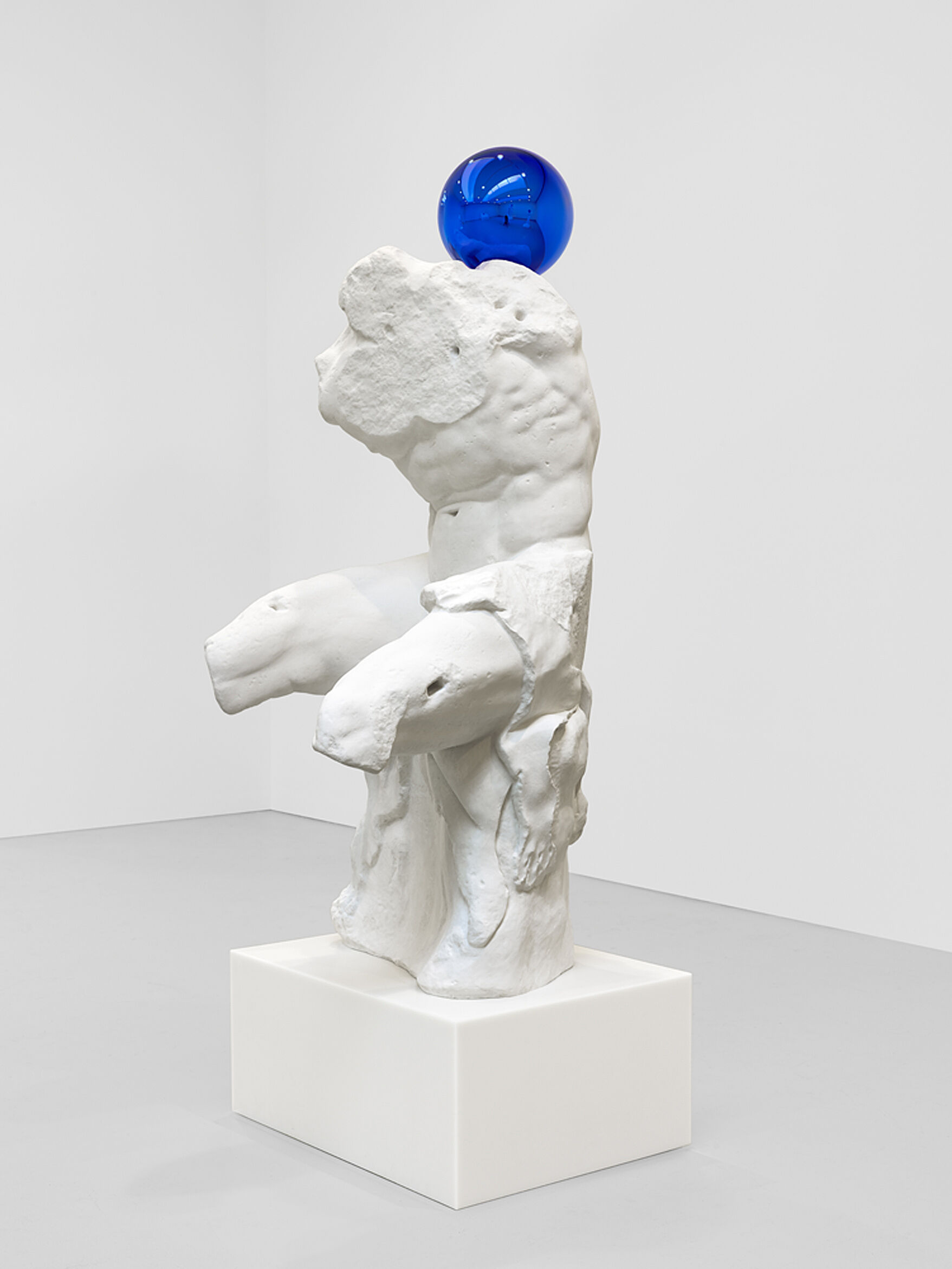 A sculpture of a nude torso with a blue ball on top.
