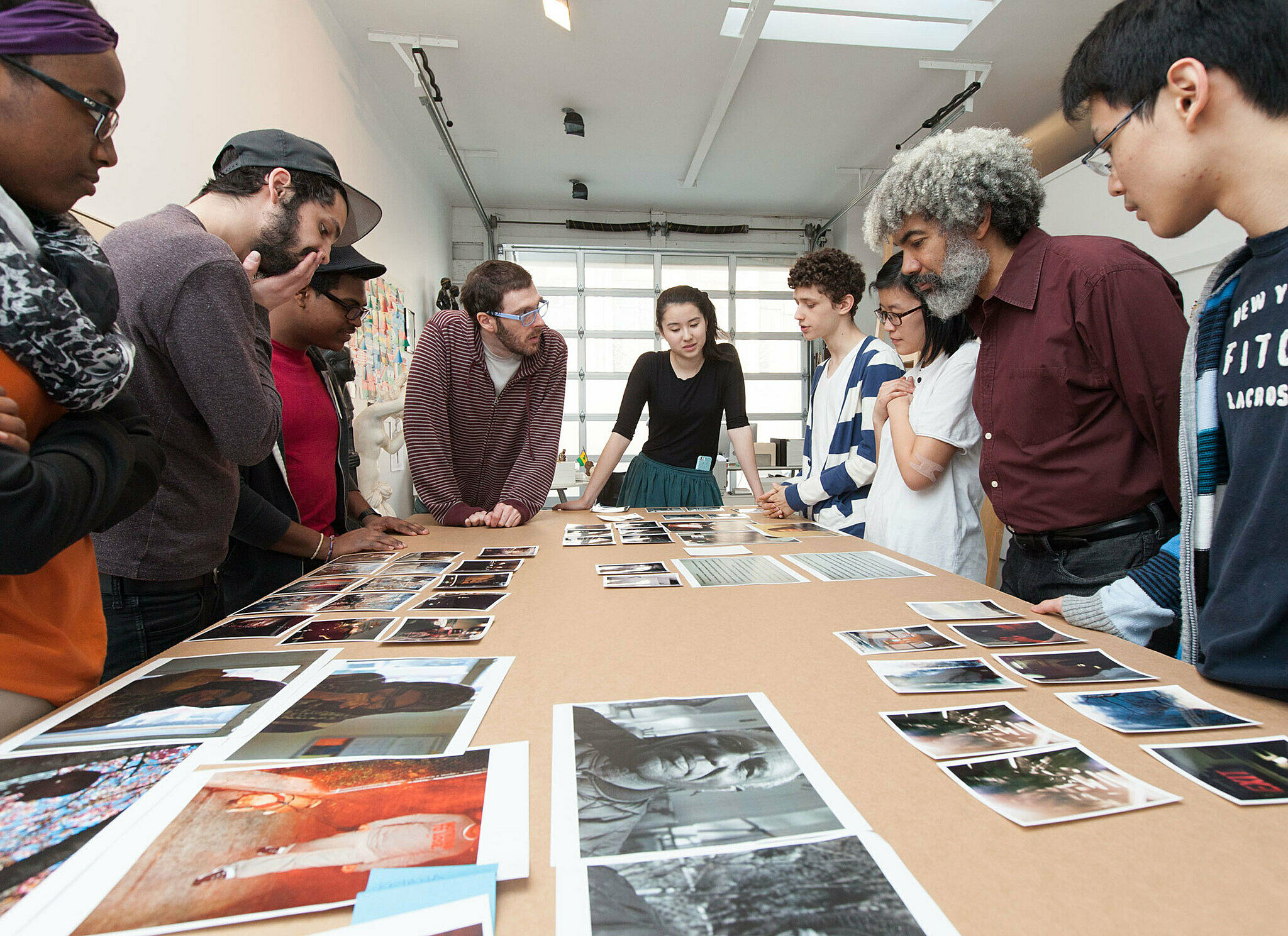Artist looks at his photos on table with students.