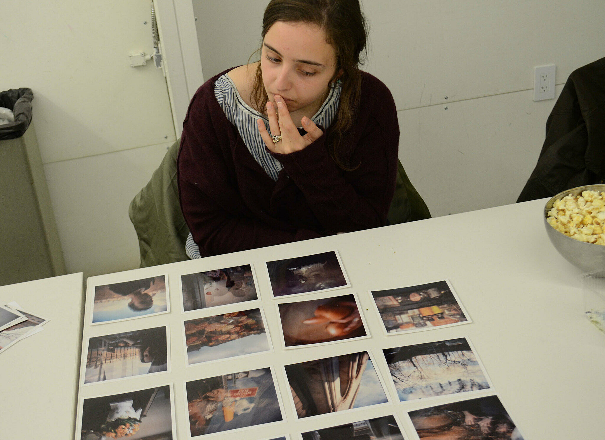 Student looking at grid of pictures on table.