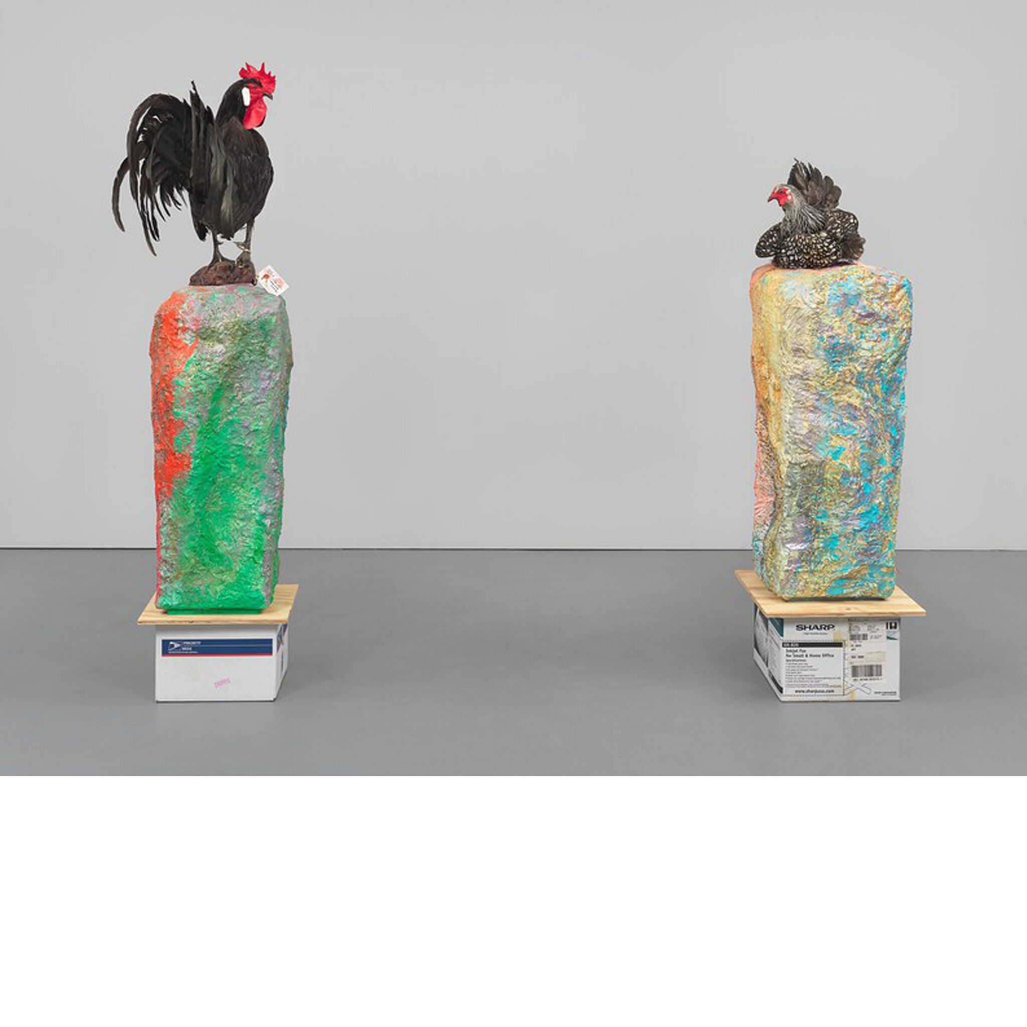 Rooster and chicken statues on top of colorful tablets.