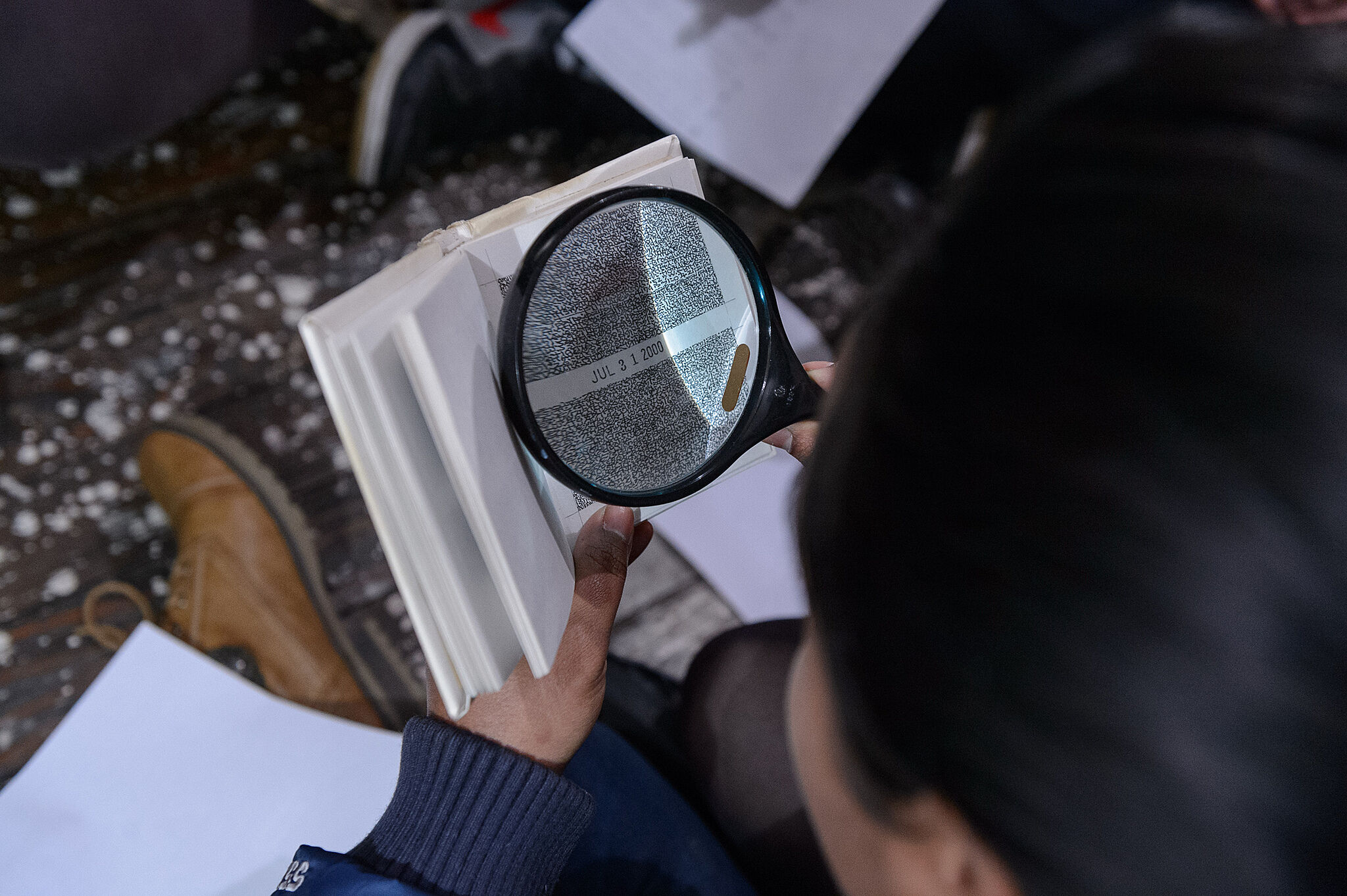 student with magnifying glass looking at a book