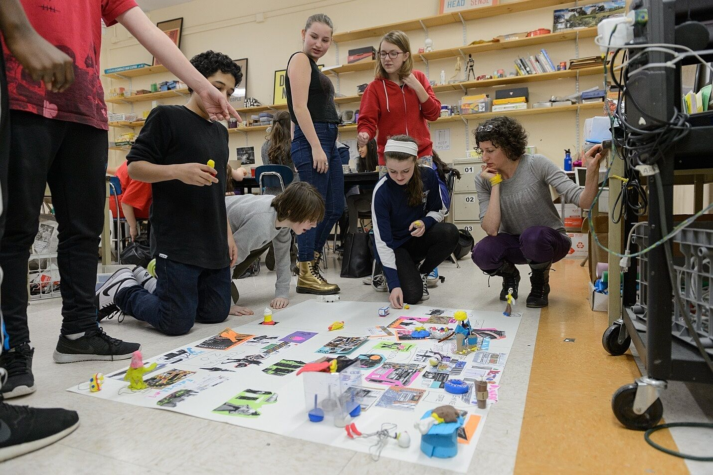 A group of students gathers around their map collage on the floor.