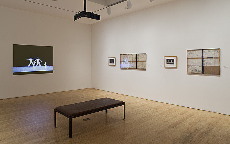 A bench in the middle of a gallery with artworks on the walls.
