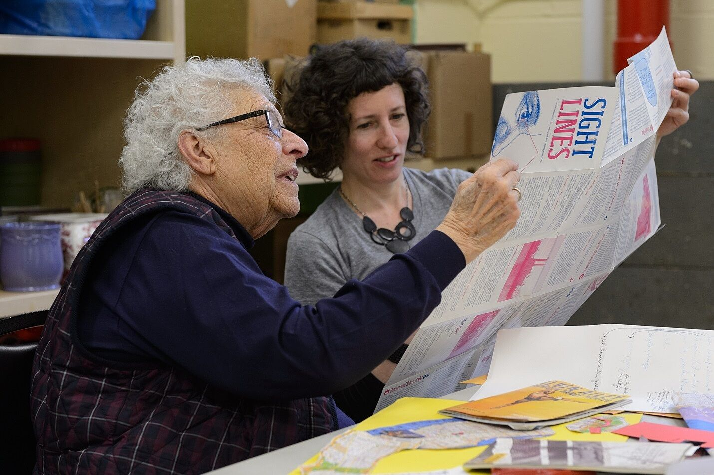 Artist Lize Mogel works on a map project with a senior citizen