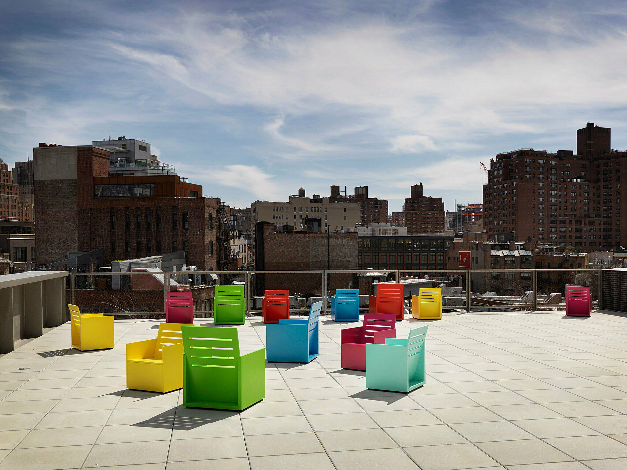 Mary Heilmann's installation on the terrace. Colorful, blocky chairs are clustered in loose groups.