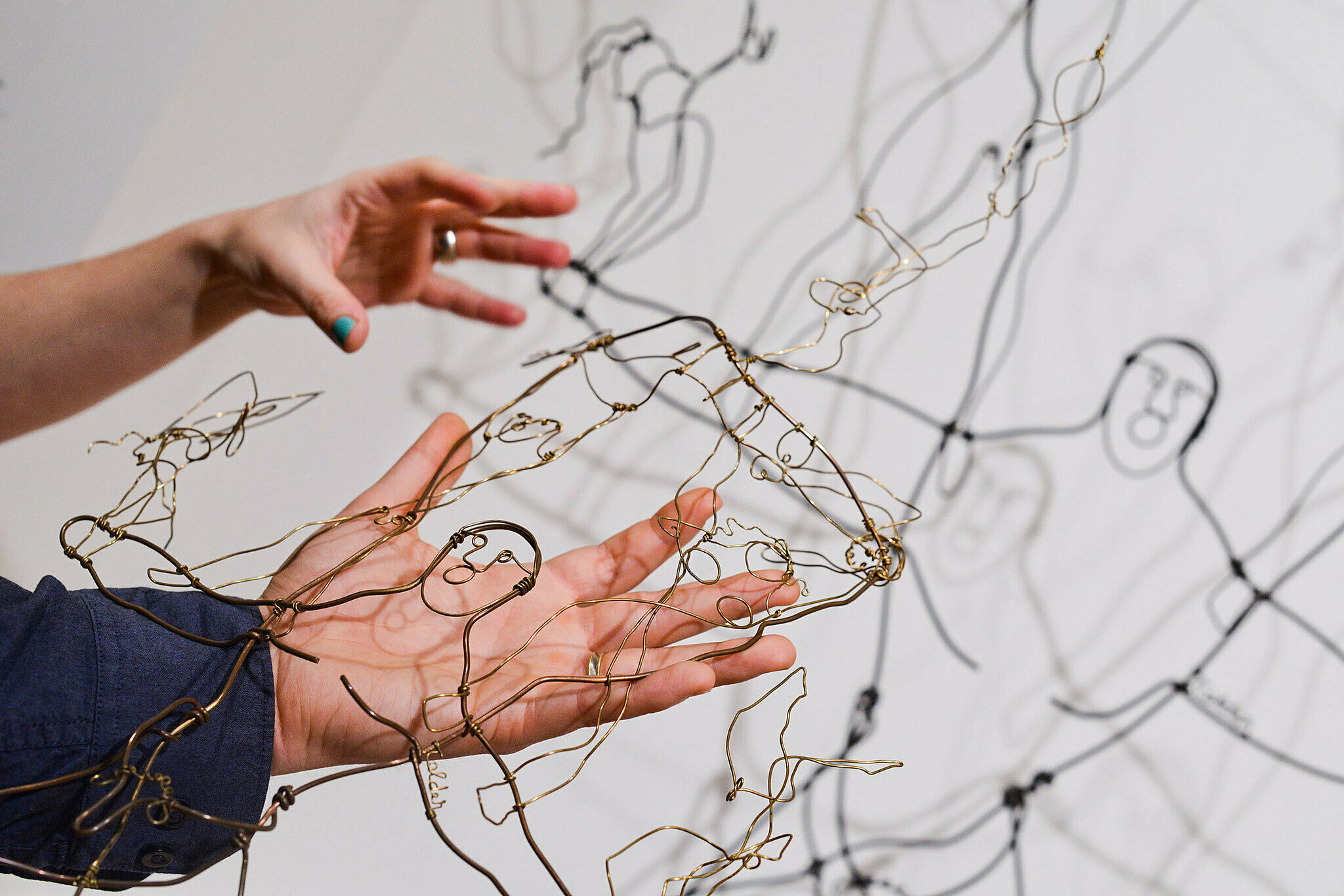 Hands hold a touch object of Alexander Calder's wire sculpture The Brass Family